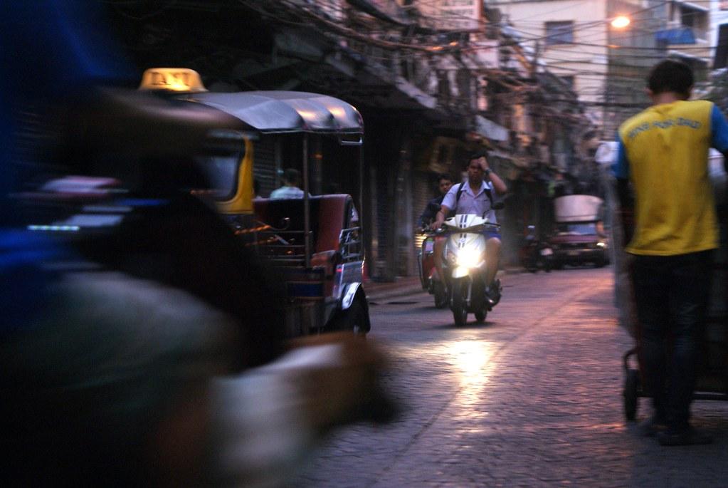 Dans la circulation, scooters, tuk tuk, voitures et piétons se freinent un passage.