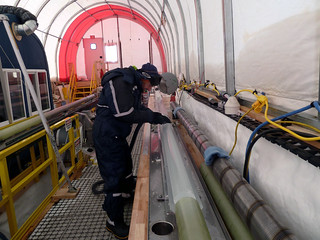 Eric Steig cleaning the run of core from 1600 meters depth | by U.S. Ice Drilling