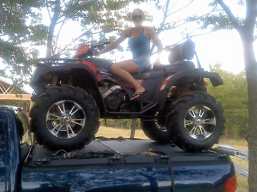 A Woman On An Atv Poses Atop A Heavy Duty Truck Bed Cover