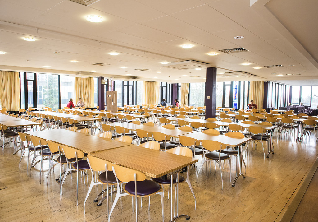 The main seating area in Claverton Rooms. Tables and seats are laid out in rows.