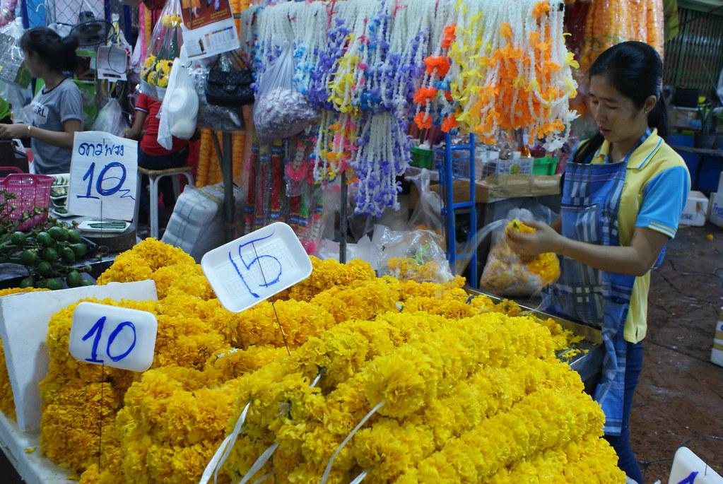 Préparation des couronnes d'offrandes par une ouvrière du marché aux fleurs à Bangkok.
