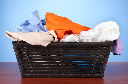 Bright clothes in laundry basket, on color background | by aqua.mech