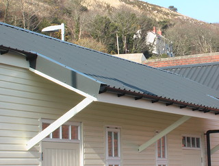 Close-up of the new building at Fishguard & Goodwick station, showing the wrong roof and wall materials and crazy angle of canopy supports.