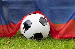 Soccer ball on grass covered with Russian flag | by wuestenigel