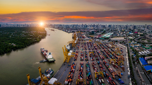 Aerial view of international port with Crane loading containers in import export business logistics with cityscape of Bangkok city Thailand at night | by MongkolChuewong