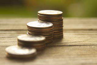 Increasing stacks of coins on weathered wood | by QuoteInspector.com