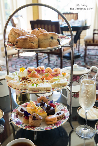 Glass of Champagne and tier of tea sandwiches and pastries | by thewanderingeater