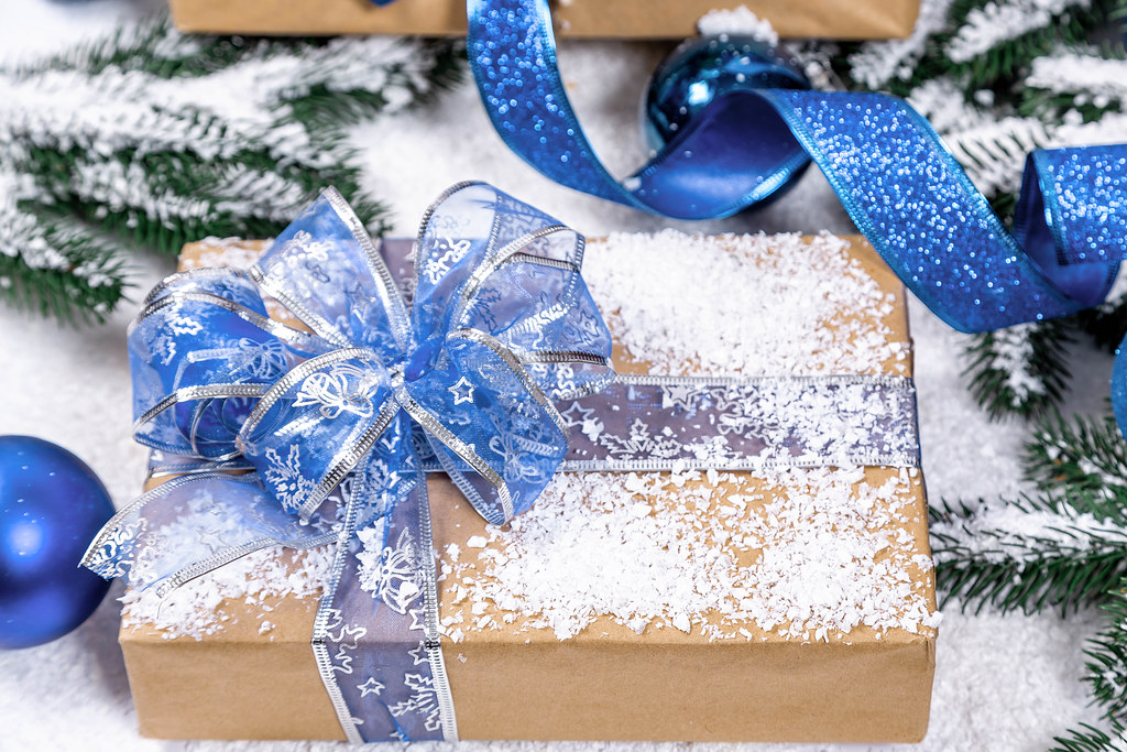 gift box with blue ribbon and bow toys and decor on new year background
