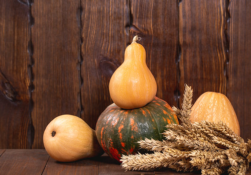 Beautiful pumpkins and wheat spikelets on old wooden background | by wuestenigel