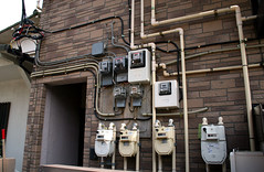 A great mess of utility meters on the side of a building.