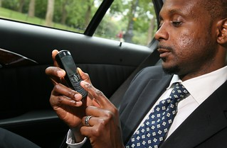 Businessman using Windows Mobile device in taxi | by gailjadehamilton