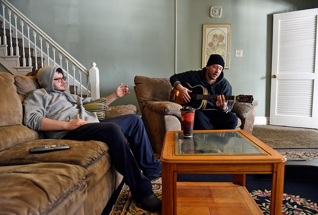 © 2016 by The York Daily Record/Sunday News. Zachary Moser, 21, of Montgomery County, Pa., chats as Nathan Embry, 27, of Lancaster, plays guitar in the Sees-the-Day recovery house where they live on Linden Avenue on Wednesday, Feb. 3, 2016.