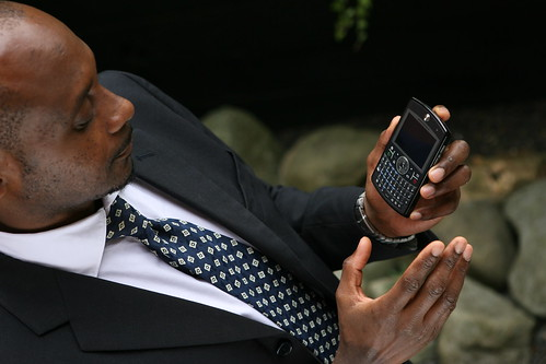 Businessman using Windows Mobile device with rocks in background | by gailjadehamilton
