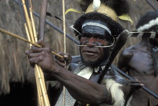 Portrait of a traditional tribal warrior holding a bow. Indonesia | by World Bank Photo Collection