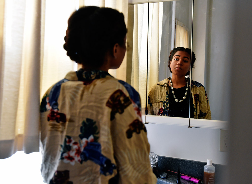 © 2016 by The York Daily Record/Sunday News. Morgan Washington-Henry glances at her reflection on her new apartment's bathroom mirror as she unpacks Wednesday, Sept. 21, 2016, in York.