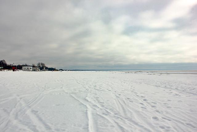 Una playa cubierta de nieve con el mar congelado.