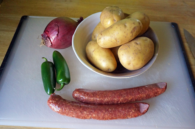 Ingredient still life: laid out neatly on a cutting board, a papery red onion, crisp green jalapeños, a bowl of yellow potatoes, and two long, plump red smoked sausages
