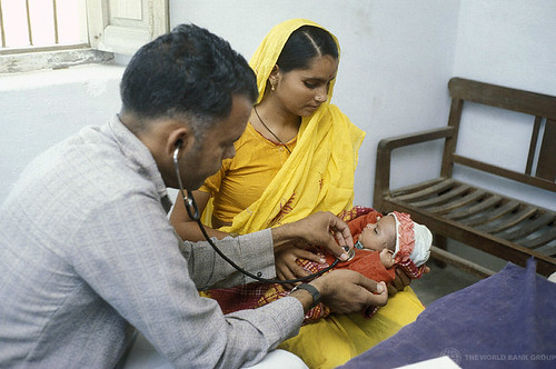 An infant receives a medical checkup | by World Bank Photo Collection