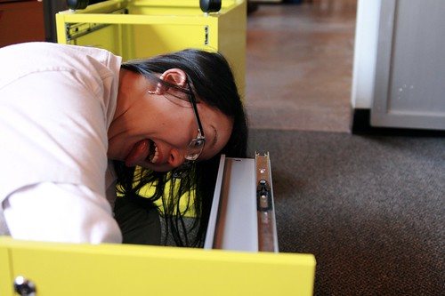 Carie, making faces while assembling IKEA furniture | by massdistraction