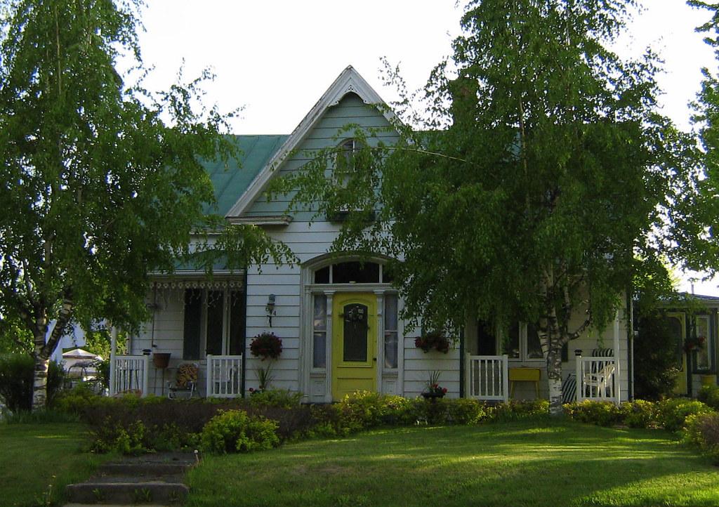 Une maison blanche avec une porte jaune et un toit vert for Portent une maison lacustre