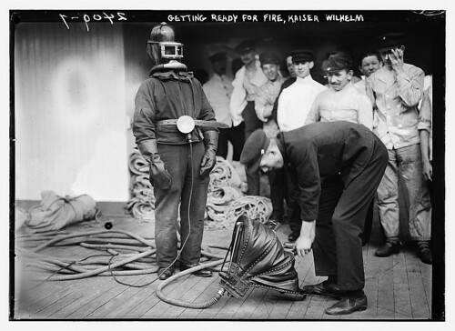 Black and white image of men standing around man in old fire fighter suit and air being pumped to him through a hose