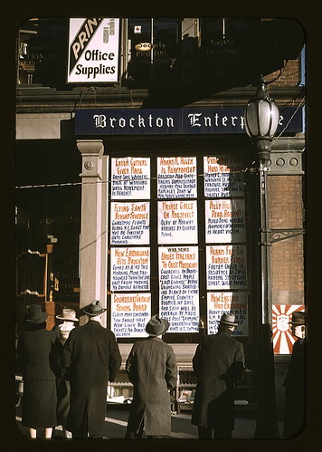 Men and a woman reading headlines posted in street-corner window of Brockton Enterprise newspaper office on Christmas Eve, Brockton, Mass.  (LOC) | by The Library of Congress