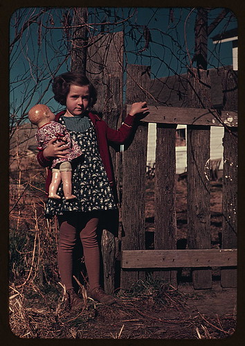 [Girl with doll standing by fence]  (LOC) | by The Library of Congress