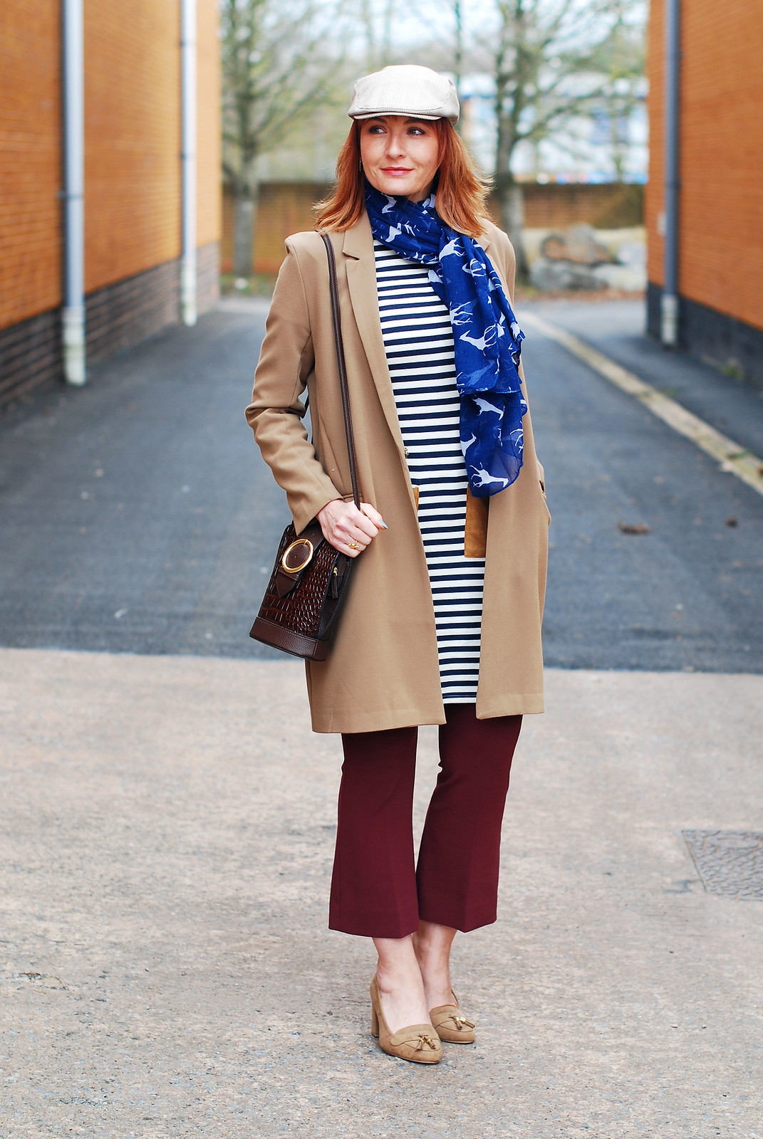Styling a preppy stripe summer dress in autumn/winter: Camel longline blazer  stripe tunic dress with patch pockets  kick flare burgundy trousers  heeled loafers  crossbody bag  stone flatcap for women | Not Dressed As Lamb, over 40 style