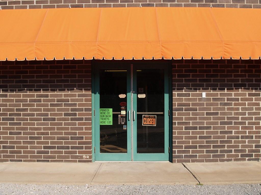 Orange Awning Green Gun Bash Sign At The Closed Hardware