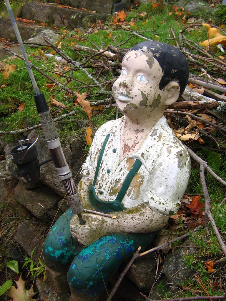 Disturbing fishing boy statue an old fishing boy statue for Little boy fishing statue