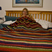 Deb finishing her stripey blanket, on bed