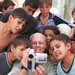 Photographer takes and shows digital video images of himself and young children. Tajikistan