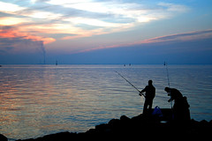 A silhouette of men fishing on the shore of a large lake.