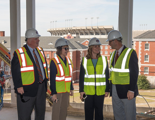 Timothy Boosinger, Marcia Boosinger, Diane Boyd and Jim Carroll stand in front of large glass windows that offer a view of the Quad and the stadium.