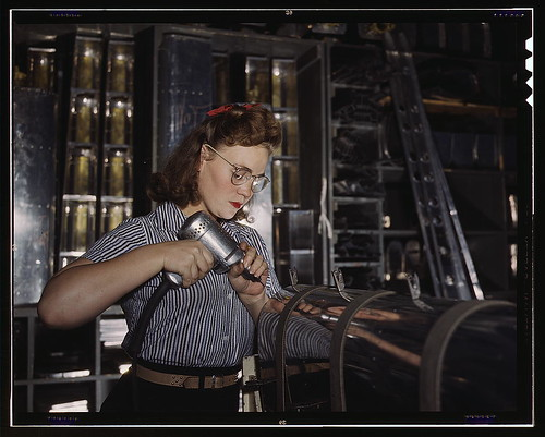 Operating a hand drill at the North American Aviation, Inc., [a] woman is in the control surface department assembling a section of the leading edge for the horizontal stabilizer of a plane  (LOC) | by The Library of Congress