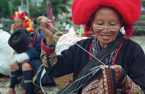 Red Zao woman embroidering a shirt at the weekly market in Sapa. Vietnam | by World Bank Photo Collection