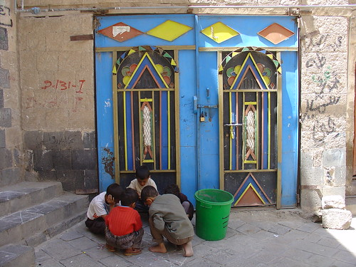 Children playing before a modern iron door in Sanaa | by olga_rashida