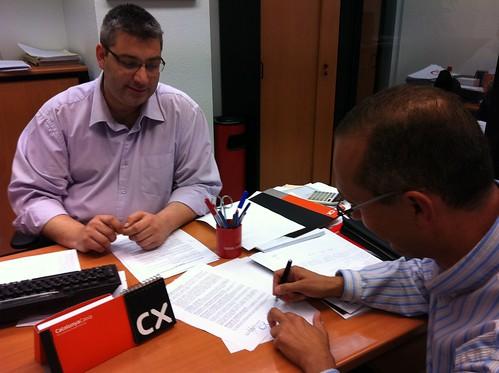 En oficina caixa catalu a firmando convenio ayuda a ru for La caixa oficina internet