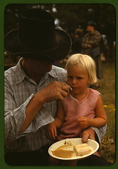 Homesteader feeding his daughter at the Pie Town, New Mexico Fair free barbeque  (LOC) | by The Library of Congress