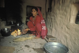 A woman cooks a meal inside her home | by World Bank Photo Collection