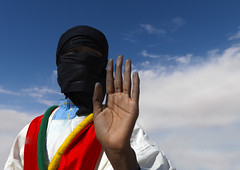 Veiled Tuareg man waving to the camera, Libyan desert | by Eric Lafforgue