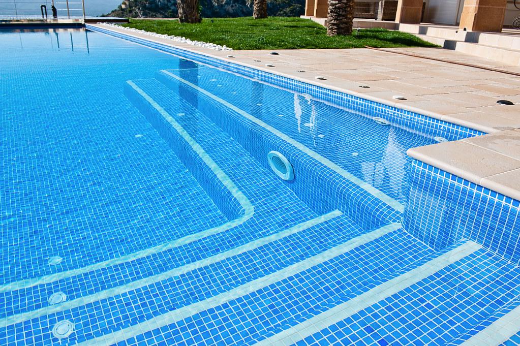 Escalera y banco de masaje piscina infinity con vistas for Gunitec piscinas