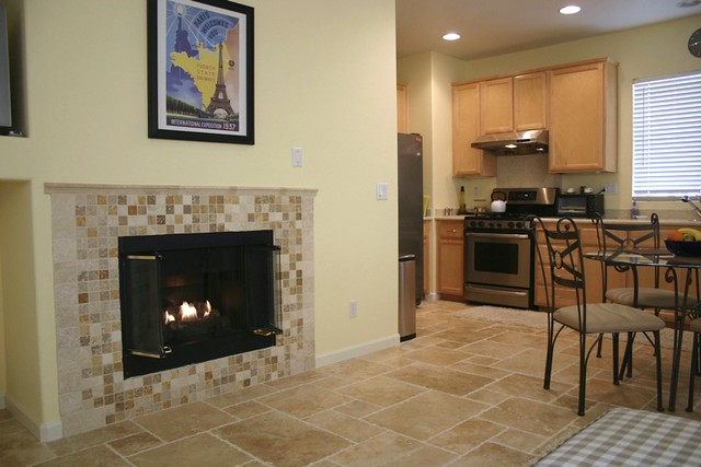 Do-it-yourself kitchen/family room floor and fireplace surround renovation featuring travertine tile.