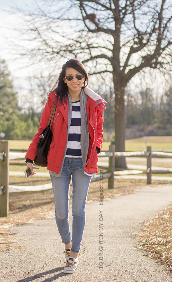 red performance jacket, gray open cardigan sweater, navy rugby striped top, lightwash skinny jeans, canvas sneakers