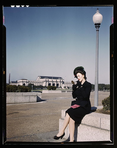 Woman putting on her lipstick in a park with Union Station behind her, Washington, D.C.  (LOC) | by The Library of Congress