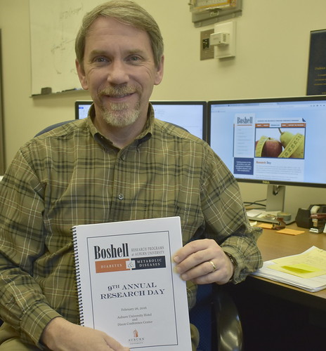 Professor Robert Judd displays a printed program from last year's Boshell Research Day.