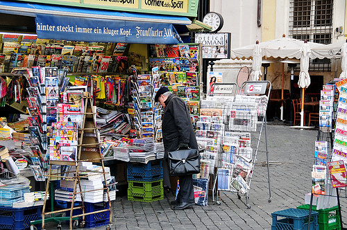A magazine stand attendant reads the paper. - MetroScenes.com ...