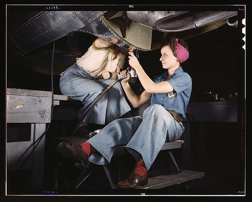 Woman working on an airplane with another worker.