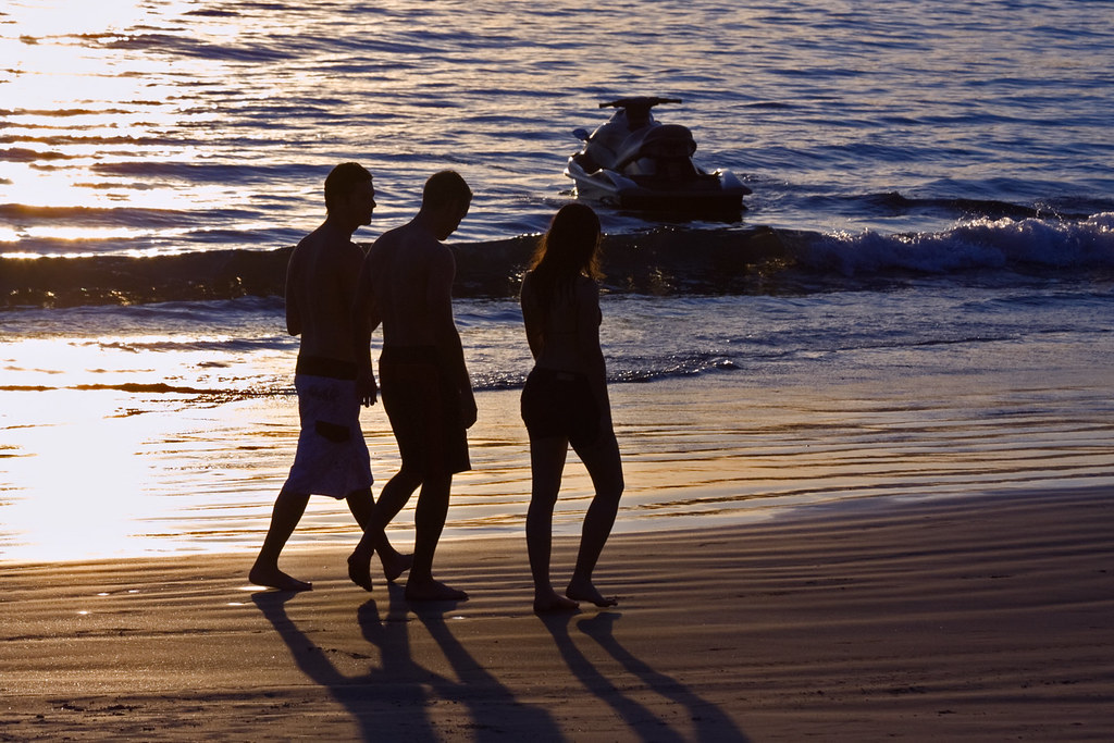 Two Boys And One Girl Passing By A Jetski On The Beach