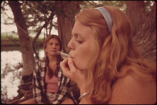 One Girl Smokes Pot While Her Friend Watches During an Outing in Cedar Woods near Leakey, Texas.